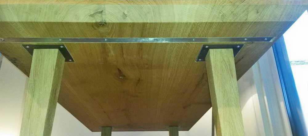 Esszimmertisch Eiche. Befestigung Füße an Tischplatte mit eingelassenem Edelstahl. Eingelassene Gratleiste.