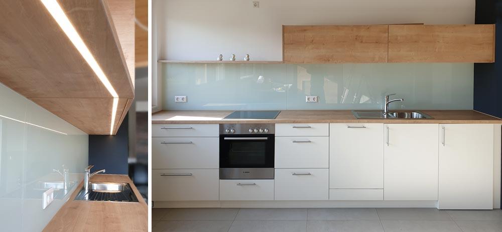Küche mit Glasrückwand und beleuchteten Oberschränken